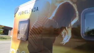 Tryck på en solig silhuett av två barn på sidan av en husbil där det också står perhelinja.