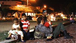 Venezuelalaisperhe istuskelee pimeässä illassa. Vanhemmat ja kaksi lasta.