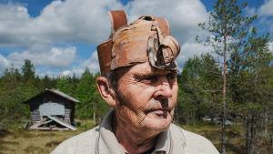 Erkki Kalliomäki päällään kyläpäällikön asu, tuohesta tehty päähine, puinen kaulakoru, pellavainen paita. Taustalla suomaisema, kuvattu Nummijärven Kammi-kylässä.
