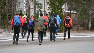 Joggare i färggranna kläder promenerar iväg med raska steg.