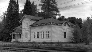 Mustavalkoinen arkistokuva vanhasta puisesta rautatieasemasta.