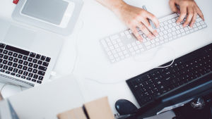 En person jobbar med flera datorer vid ett bord.