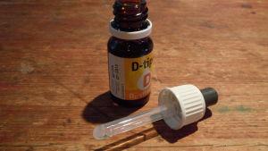 D-vitamindroppar i brun flaska på brunt bord.
