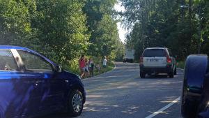 Barn på väg med bilar i en kurva.