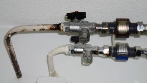 Kondensvatten droppar från gammalt rostigt rör i en bostad.