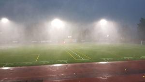 Det regnar hårt över fotbollsplanen.