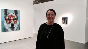Charlotta Björkendahl står framför tavlor i ett galleri.