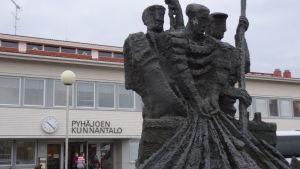 Framför kommunkansliet i Pyhäjoki står en staty till minnet av tidigare generationers arbete