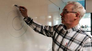 Mats Lindberg ritar en cirkel på tavlan.