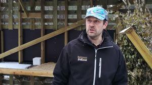 En man med keps står framför ett matningsställe för skogsrenar.
