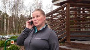 Leena Haanpää, vd för golfkubben Han-Golf i Hangö talar i mobiltelefonen. Ute är det snöfritt och gräsmattorna är lika gröna som på sommaren. Bilden tagen i januari 2018