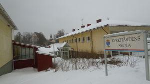 En gul skolbyggnad täckt av snö. I förgrunden syns en skylt där det står Kyrkfjärdens skola.