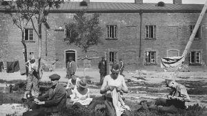 Fångar på Sveaborg 1918, syr kläder på gården