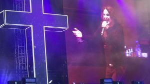 Ozzy Osbourne med stort kors på scen.