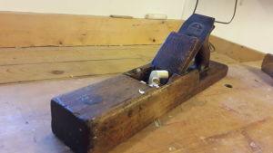 En bild av en gammal hyvel på en arbetsbänk av trä.