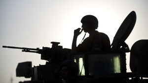 Silhouett av en israelisk soldat som sticker upp ur en stridsvagn.