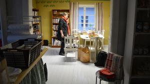 Kvinna talar i telefon i ett rum fullt av böcker.