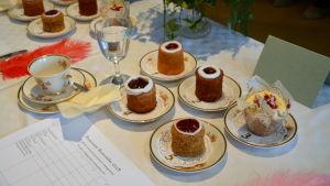 fem runebergstårtor på tallrikar med guldkant, en kaffekopp och blommor på bord med vit duk