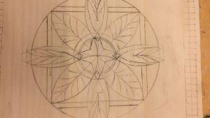 Skiss av ett ornament i blyerts på en ljus träskiva.