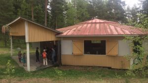 Ett gult hus med rött tak på Gumnäs festplats i Pojo.