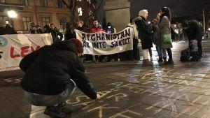 Demonstration där en man skriver på gatan och i bakgrunden tiotal personer och plakat om att Afghanistan inte är säkert.