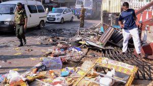 polis i Sri Lanka utanför en förstörd butik i distriktet Kandy 6.3.2018.
