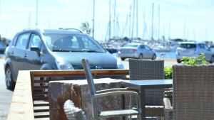 Del av en uteservering med bord och stolar, en parkeringsplats syns i bakgrunden. Bokom parkeringsplatsen är det hav och segelbåtar. Det är en vacker sommardag.