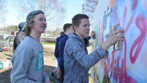 Eddi Bussman målar graffiti på Raseborg offspring 2016. Milton Holmqvist till vänster.