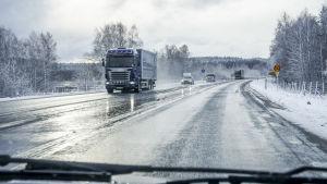 Lastbilar och personbilar på en våt landsväg på vintern.