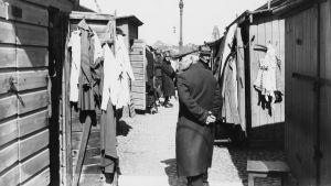 Man på Narinkens köpplats, mellan låga hus. 1920-tal