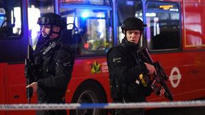 Beväpnad polis framför en röd buss efter falsk alarm om en terrorattack vid metrostationen Oxford Circus i London.