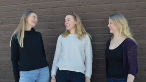 Tre kvinnor står framför en trävägg. De tittar på varandra och skrattar. De är utomhus.