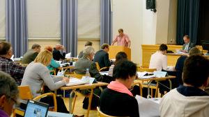 Ledamöter under ett fullmäktigemöte i Raseborg. SFP:s Björn Siggberg står i talarstolen.