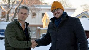 Larson Österberg skakar hand med Robert Louhimies. De är fotograferade utomhus och husen bakom är täckta med snö.