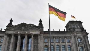 Riksdagshuset i Berlin. I förgrunden ser man den tyska flaggan vaja i vinden.