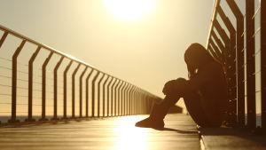 Person sitter ensam på brygga i solnedgången.