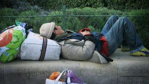 En hemlös man ligger och sover på en mur.