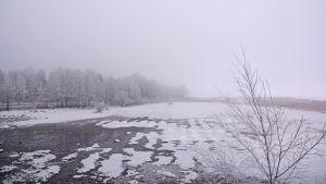 grå himmel ovanför nästan istäckt mark