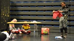 Skådespelarna för Kalabalik i Komposten övar på scen. En av dem håller i ett par vitprickiga röda kalsonger.