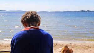 kvinna sitter på sandstrand