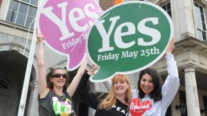 Tre kvinnor håller upp plakat för att fira att ja-sidan segrade i den irländska folkomröstningen om abortlagar i maj 2018.