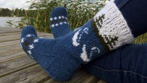 Fötter med stickade sockor på en brygga med vass i bakgrunden.