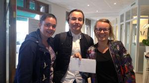 Fredrika Åkerö, Emil Thuesen och Malin Valtonen står och poserar med ett kuvert där det står med små bokstäver Raseborg Pride.