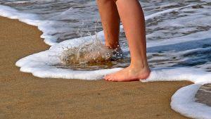 Bara fötter i sanden vid en strand