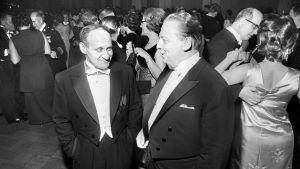 Författaren Väinö Linna samtalar med journalisten Nils-Börje Stormbom (t.h.) på självständighetsfesten på presidentens slott 1968.