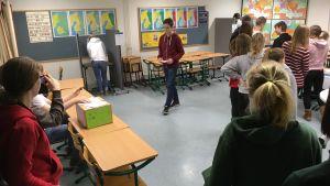 Elever står i ett klassrum som är en vallokal.