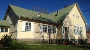 Ett gult trähus med grönt tak som är det före detta kommunhuset i Tenala.