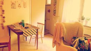 Ett brunt bord med rutig duk och två stolar bredvid. I förgrunden en vit fotölj med en mönstrad kudde.