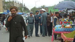 Kabulbor och poliser vid stånden på en gata i centrala Kabul.
