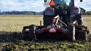 Traktor plöjer en åker.